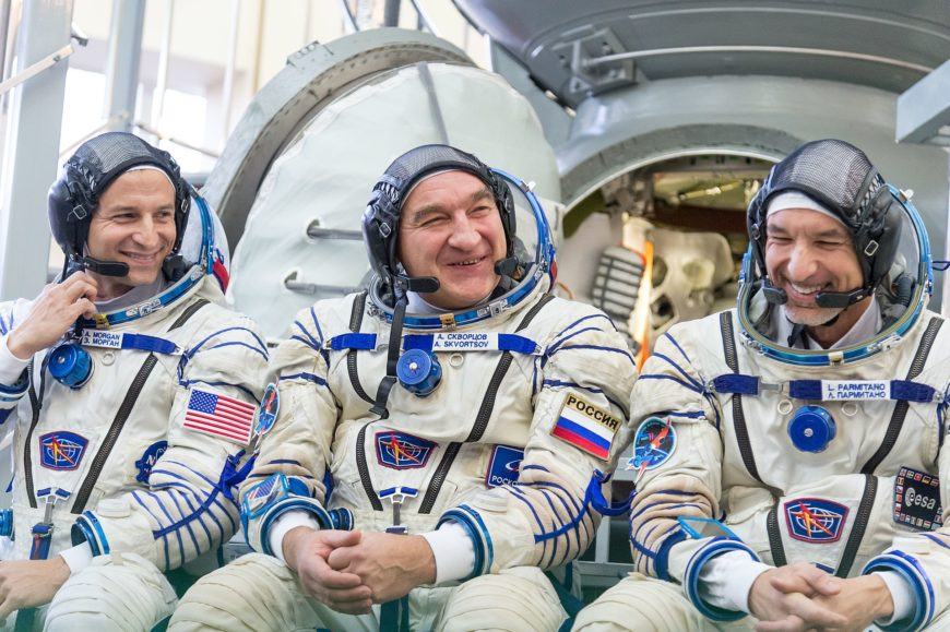 1920px-Soyuz_MS-11_backup_crew_in_front_of_the_Soyuz_spacecraft_mockup-870x579
